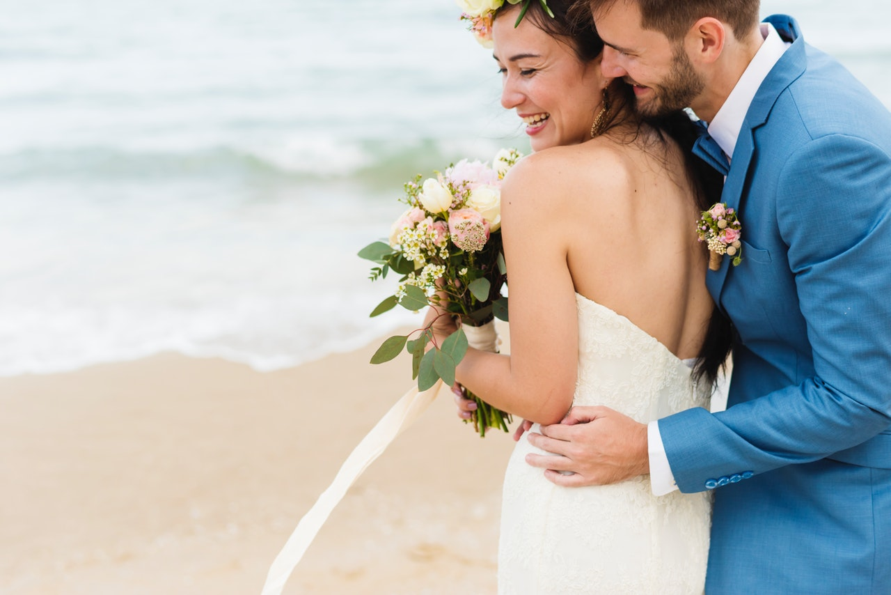 Couple smiling on the beach after getting married.